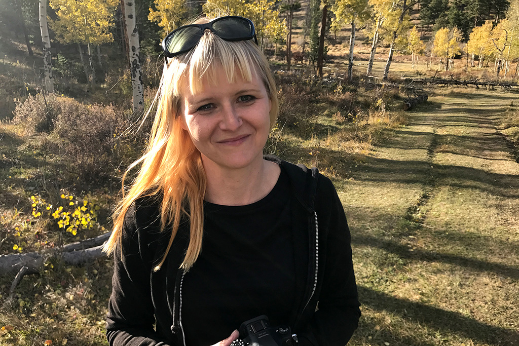 Luci Westphal (documentarian and Happier Place founder) among the autumn colors in the Colorado mountains.