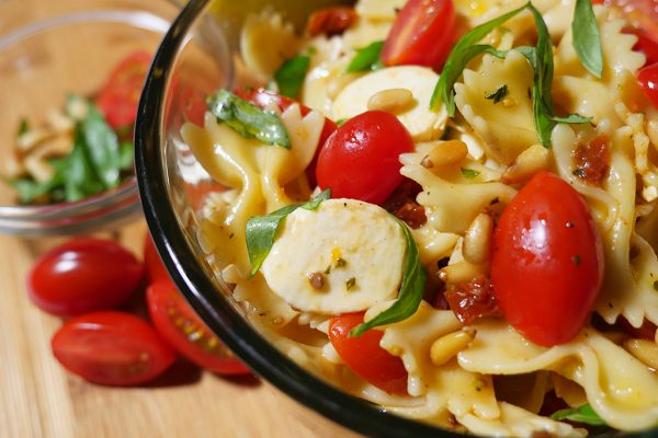 Favorite picnic food: Happier Pasta Salad recipe features tomatoes, mini mozzarella, sun-dried tomatoes and toasted pine nuts.