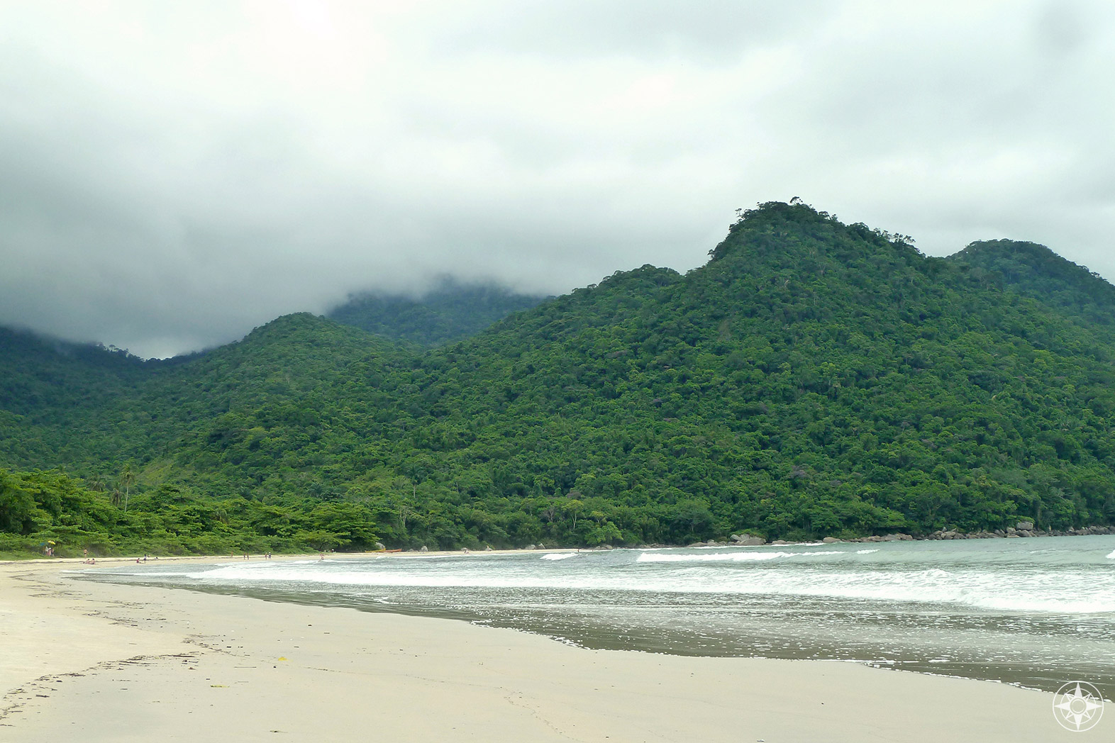 Atlantic rainforest covered hills disappearing into the clouds behind large and mostly empty Dois Rios beach on Ilha Grande, Brazil. Happier Place