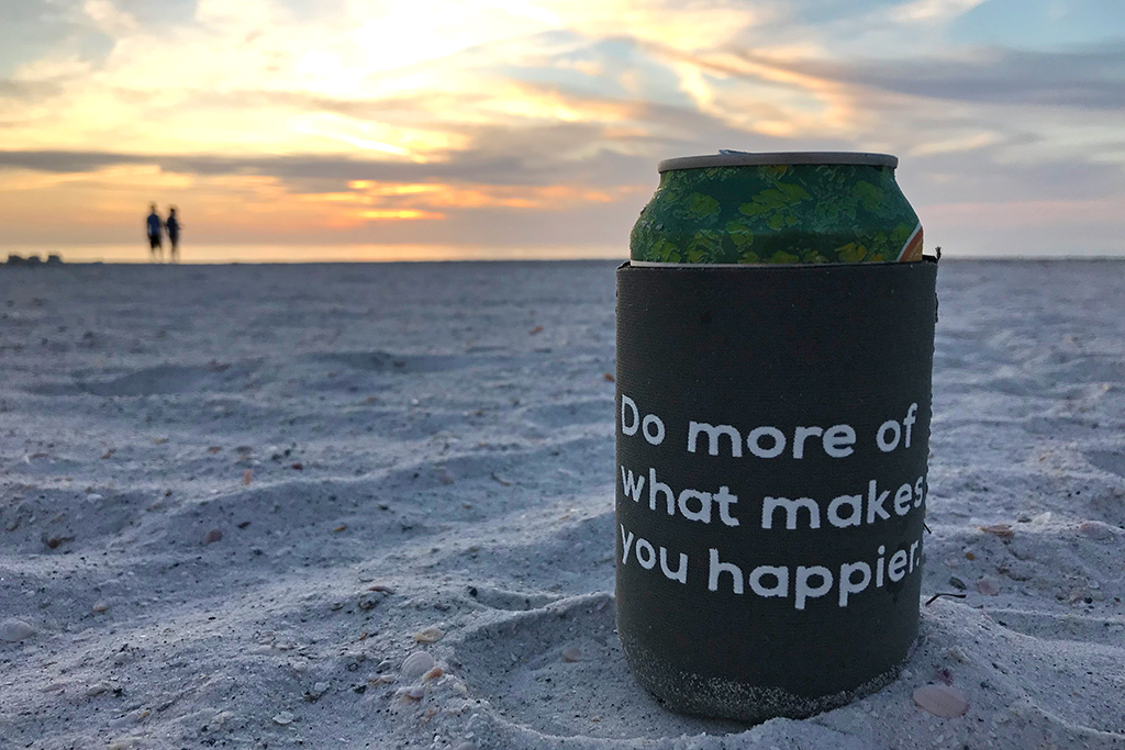Do more of what makes you happier koozie on the beach with sunset - benefit of moving to a happier place.