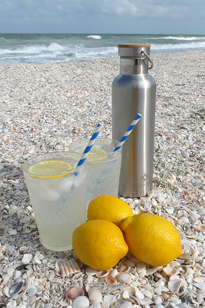 Vodka Collins and Happier Place insulated stainless steel bottle on the beach in Florida - Happier Place