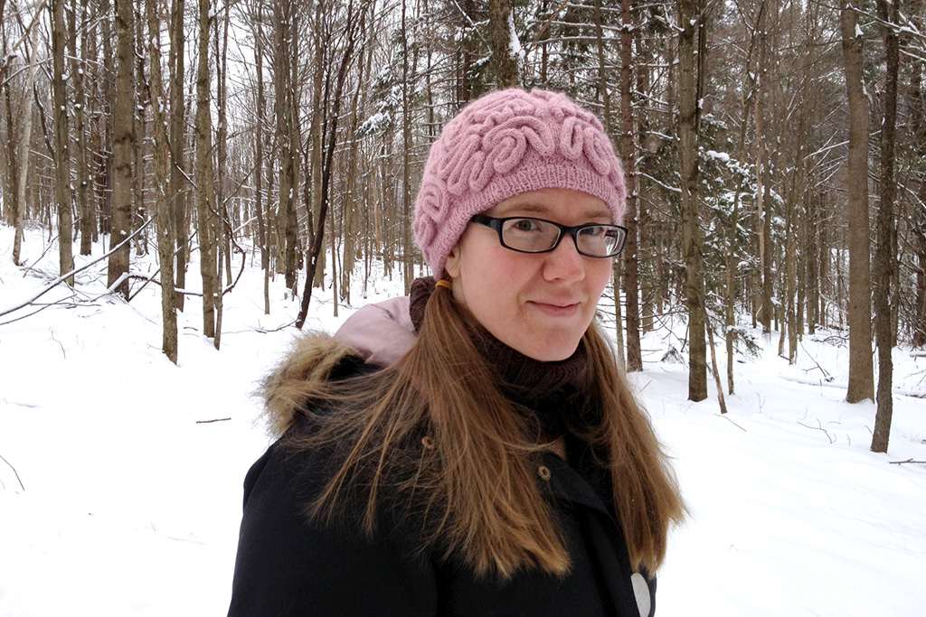 Katherine Guttman in her woods wearing a brainy hat. Happier Place