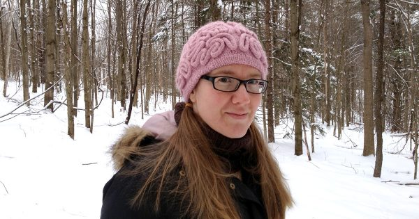 Katherine Guttman in her woods wearing a brainy hat. Happier Place - The Stitchy Crow