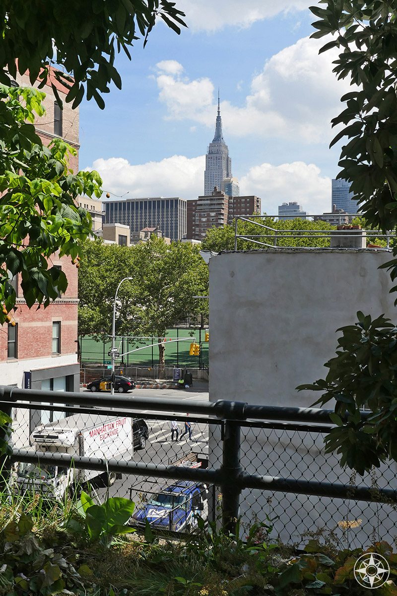 View of the Empire State Building between the trees of the elevated park The High Line. Happier Place