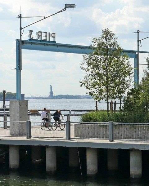 Cyclists on Pier 3 in Brooklyn Bridge Park with Statue of Liberty in the distance.