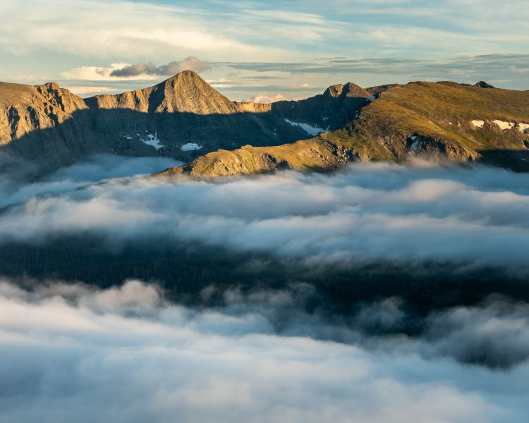 Sunny mountain peaks above the clouds. Photographer Bryan Clark