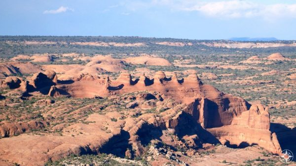Getting new context for the famous Delicate Arch as it balances at the top of a big bowl
