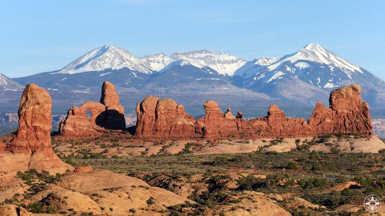 Turret Arch and other rock formation in front of the snow-covered La Sal Mountains in Utah.
