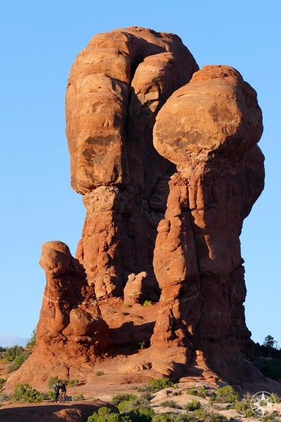 The two people in front of the sandstone rock formation give an idea of size in Arches NP.