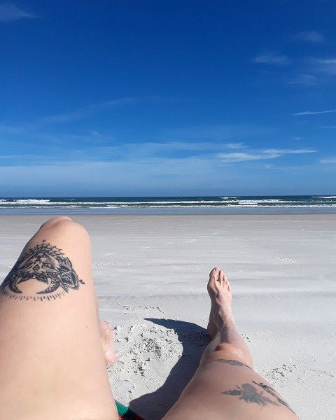 Tattooed legs on a Florida beach.