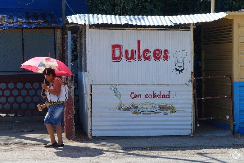 Dulces Con Calidad - Quality Sweets hut in La Boca Cuba and woman using umbrella for shade.