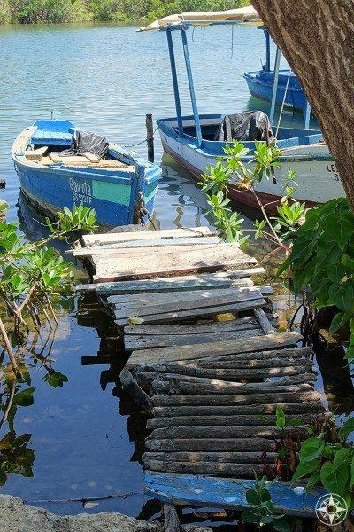 Small pier, smaller boat in the little harbor along the river in La Boca, Cuba.