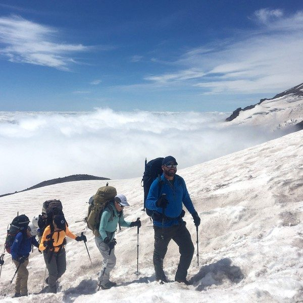 Jake Gray leading a group up snowy Mount Rainier above the clouds