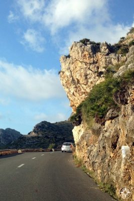 Winding road with rock overhang in the Driving through the Tramuntana Mountain on a road lined by rustic walls
