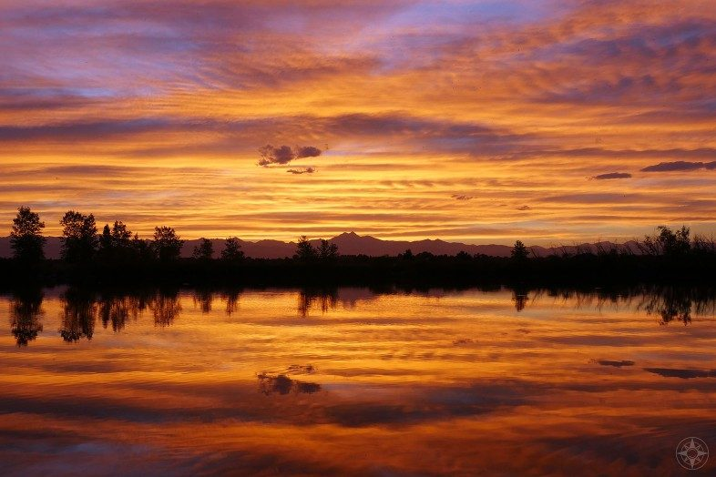 Colorado sunset reflected in pond with Rocky Mountains backdrop