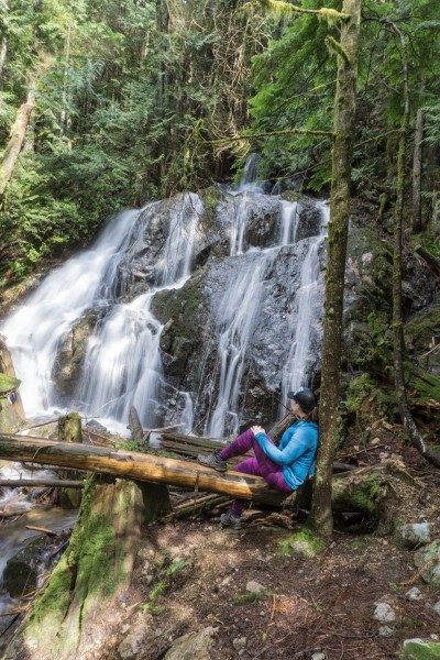 woman sitting by waterfall - Mystery Falls near Vancouver