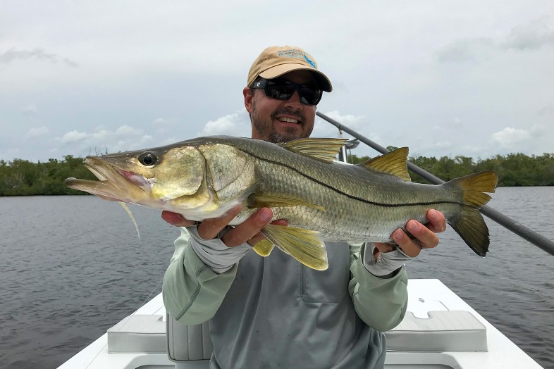 Captain Frank Praznik holds snook fish, fly fishing guide