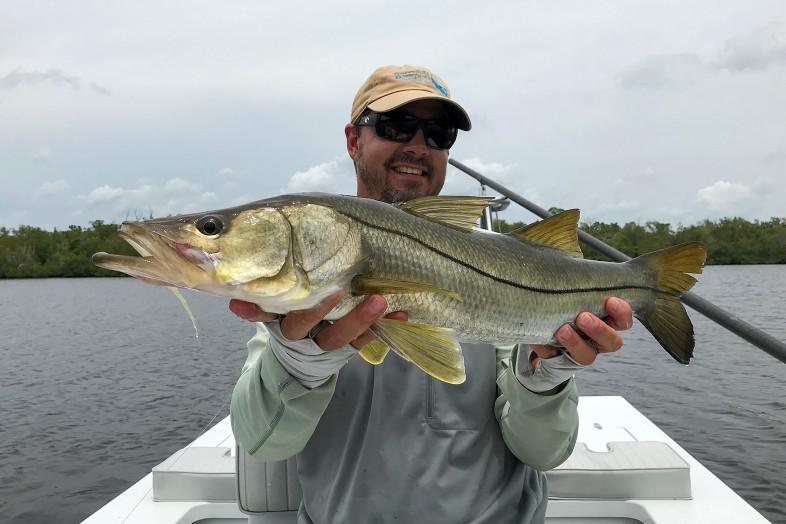 Captain Frank Praznik holds snook fish, fly fishing guide