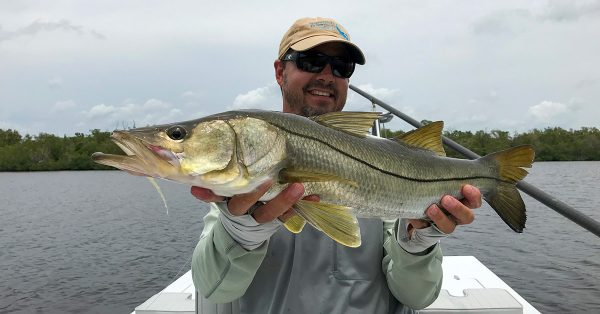 holding a snook coastal fly fishing adventures