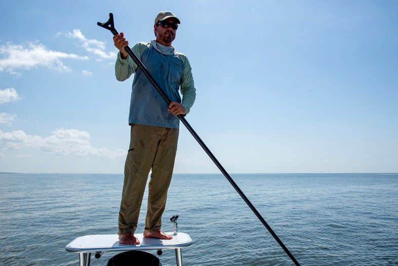 """Fly fishing guide Capt. Frank Praznik's work place: standing on the platform in the back of his skiff from where he can see the fish in the clear water and pull the boat into the ideal position for his clients to catch the big one"""""""