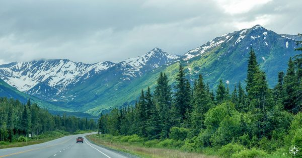 Highway 1 in Alaska on the Kenai Peninsula along snow-covered mountains and tall evergreen trees