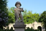 Statue of boy holding fish at Maerchenbrunnen Fairy Tale Fountain in Volkspark Friedrichshain Berlin