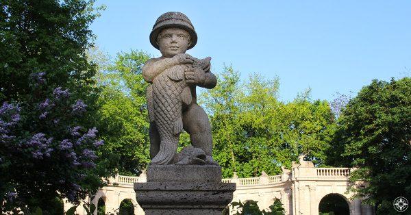 Statue of boy holding fish at Maerchenbrunnen Fairy Tale Fountain in Volkspark Friedrichshain Berlin