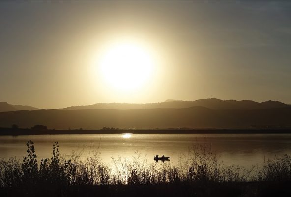 people in a boat on lake, golden hour, mountain range, postcard, Colorado