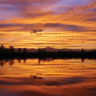 vibrant sunset sky and Rocky Mountains reflected in pond, St. Vrain State Park, Colorado, postcard