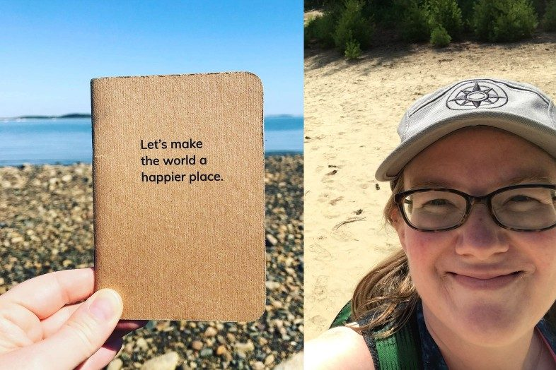 Kate showing off her Let's make the world a happier place notebook and Happier Place camper hat