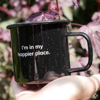 """Black speckled """"I'm in my happier place."""" enamel metal mug in its natural environment: outdoors."""