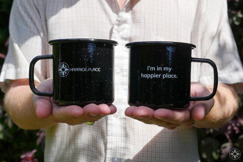 """Black speckled """"I'm in my happier place."""" enamel camping mug, front and back"""