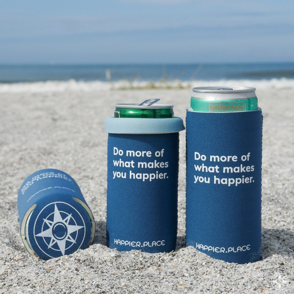 Indigo \'Do more of what makes you happier\' neoprene slim can coolie on the beach. It\'s perfectly sized for 12 oz slim cans and the shorter 8 - 9 oz slim cans. Great way to keep drinks cool like White Claw, Truly, Henry\'s, Red Bull Limited Edition, La Colombe, Simply Wines, Barefoot Wines, etc. 