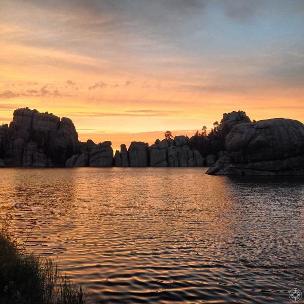 Dramatic sunset highlights rock formation wall of Sylvan Lake, Needles Highway, Custer State Park, South Dakota.