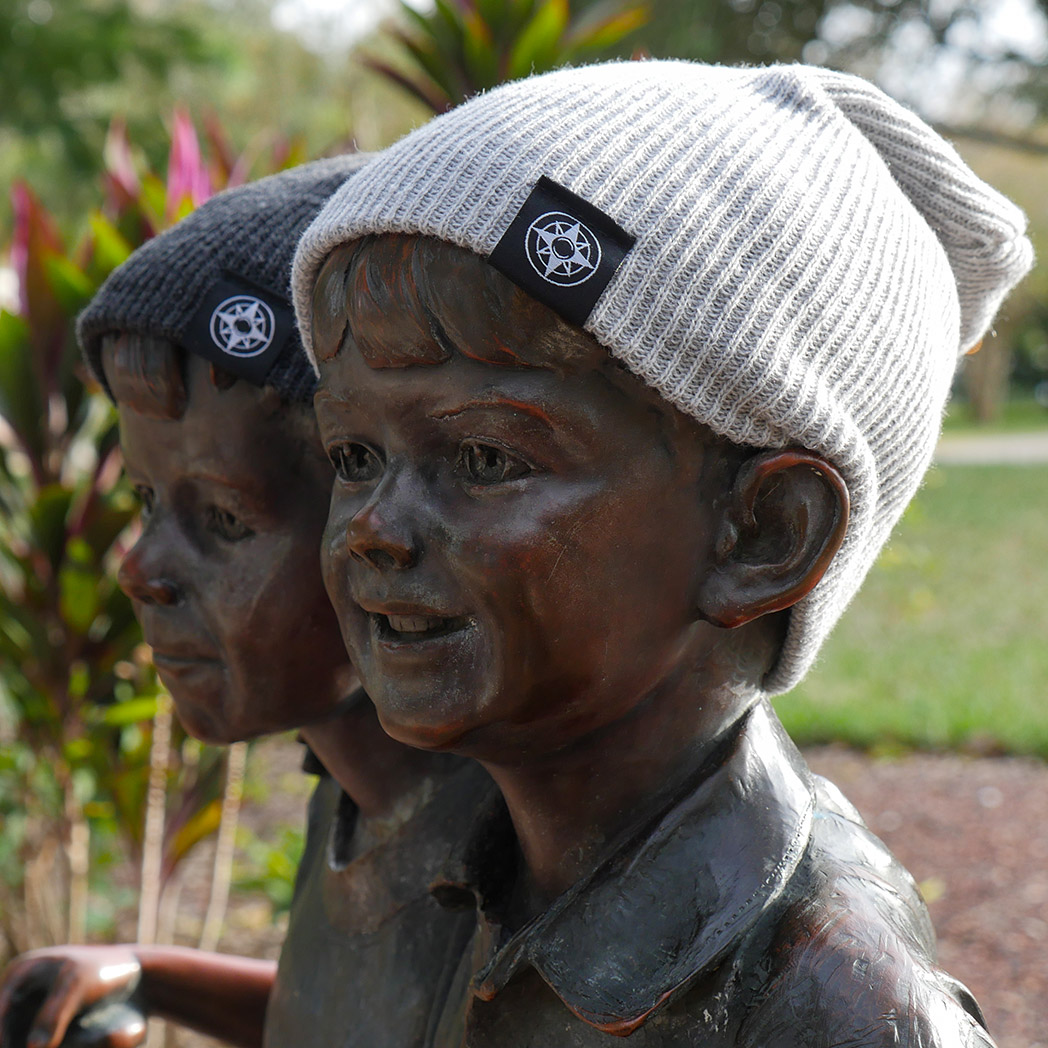 Happier Place Slouchy Beanies in light grey and, charcoal with Happier Place compass logo on fold-over cuff. Adult-sized beanies on oversized children\'s statues in Largo Central Park, Florida.  #HappierPlace #outdoorleisure #outdoorlifestyle #fallfashion #winterfashion
