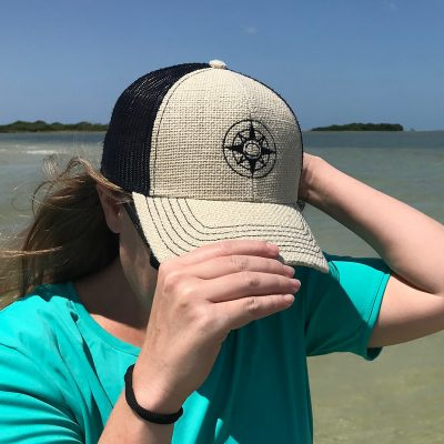 Happier Place burlap trucker hat with stitched on black compass logo