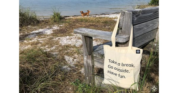 """The """"Take a break. Go outside. Have fun"""" Happier Place cotton shoulder bag hanging on beach bench in Florida. Added fun: Whiskey Dog!"""