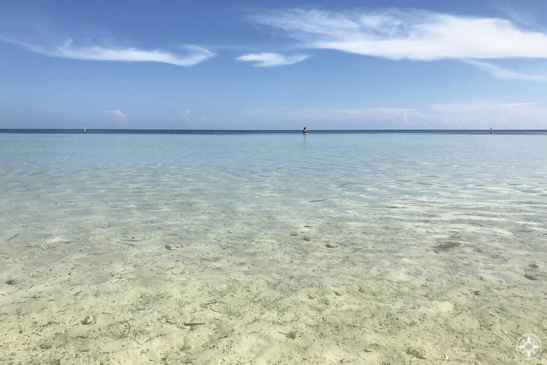 Picture yourself sitting on the beach with your feet in the shallow clear water and gazing out into the distance where the blue sky meets the sea, Florida Keys, Loggerhead Beach