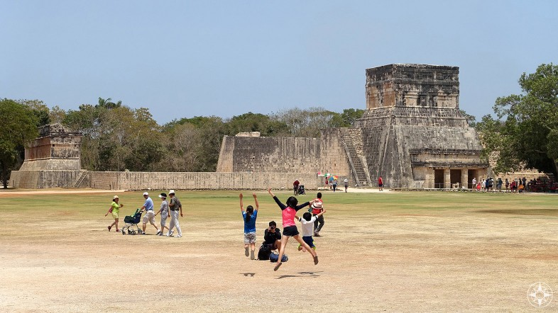 Kids jumping for photographer in front of El Juego de Pelota (Great Ball Court) and Temple of the Jaguars, Chichen Itza, Mexico