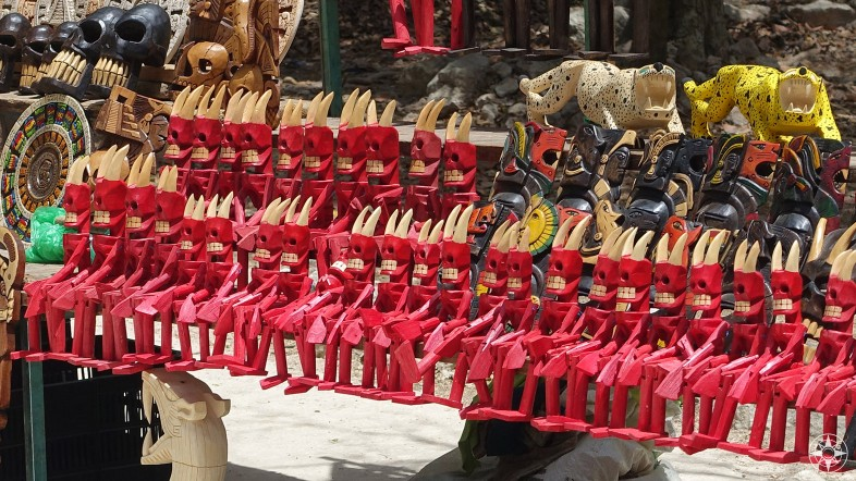 Dash of color: red wooden devils and jaguars for sale at Chichen Itza, Mexico