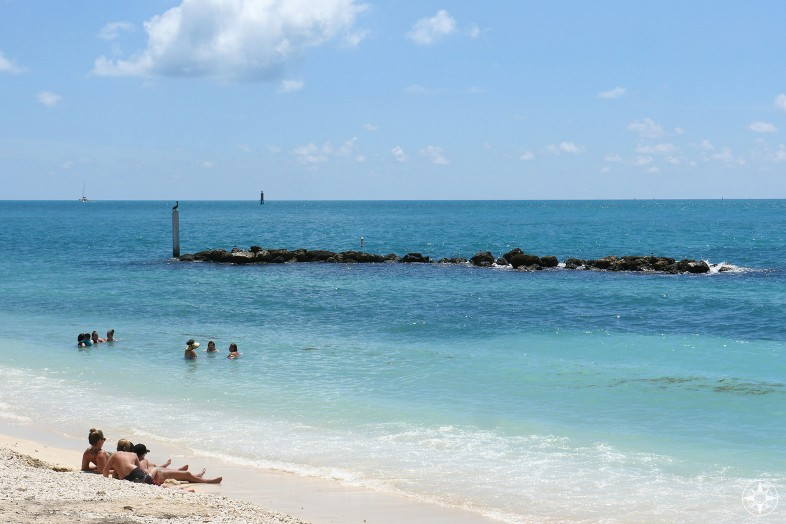 people on the beach and in the blue Key West water, rock wall inviting fish and birds and snorkelers
