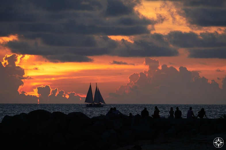Sunset with silhouetted sailboat and people watching from rock wall
