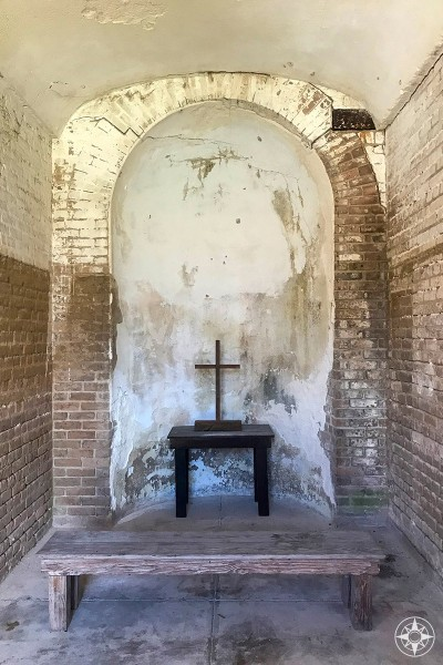 Bench, table and cross in nook inside civil war era Fort Zachary Taylor.