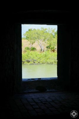 View through a window of Fort Taylor to the moat and plant life beyond.