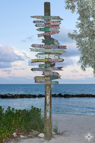 Iconic wooden destinations sign post, Miami, London, New York City, Fort Zachary Taylor Park, Key West, beach, at dusk, Happier Place