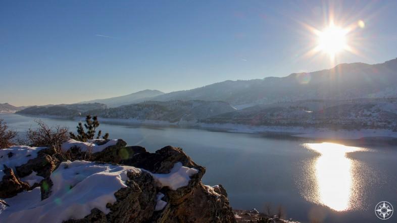 Powerful mountain sun melting snow along Horsetooth Reservoir and surrounding hills.