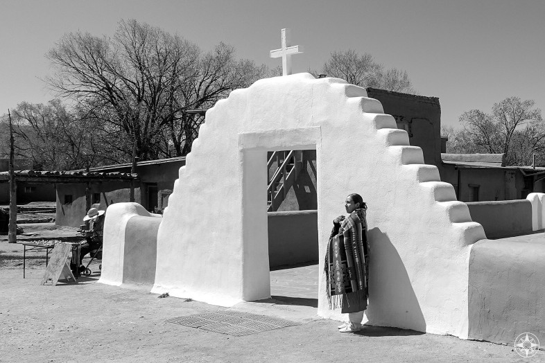 Native American woman, Taos Pueblo church, woven blanket, white wall gate with cross, merchant man, New Mexico, black and white