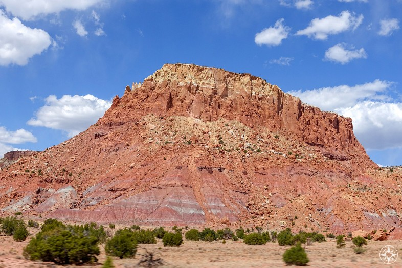 Colorful red, yellow and white mesa against blue sky along the road to ghost ranch, New Mexico