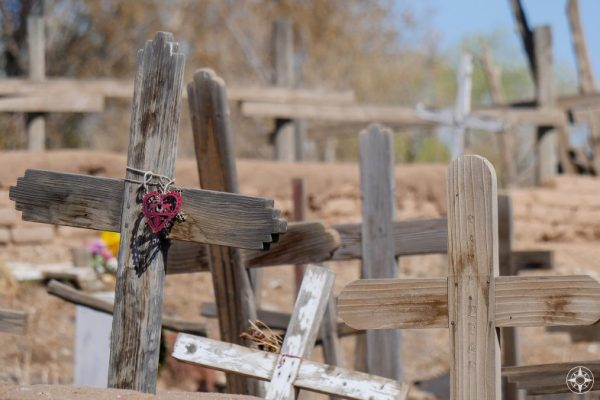 Wooden cemetery crosses and fence post crosses and a burgundy heart at Taos Pueblo cemetery, New Mexico