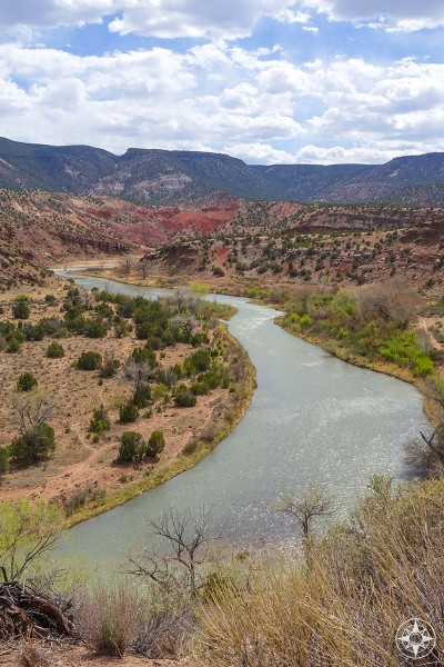 On the road to Ghost Ranch, the Rio Chama view painted by Georgia O'Keeffe as the river snakes from the mountains, between red rock hills and green shrubs.